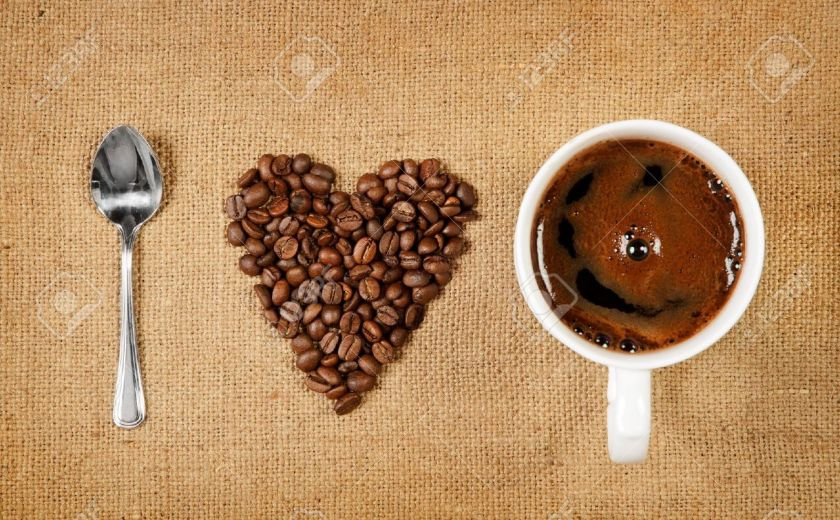 11438455-Heart-shape-made-from-coffee-beans-with-a-spoon-and-cup-of-coffee-on-hessian-spelling-I-love-coffee--Stock-Photo
